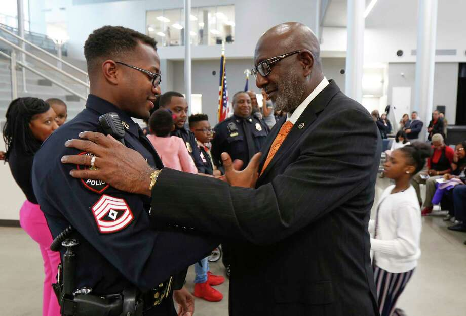Newly sworn in HISD Police Sgt. Justin Williams shakes his father's, Willie Williams, hand after the elder Williams pinned his badge on him in a formal swearing-in ceremony at the High School for Law and Justice Wednesday, Jan. 23, 2019, in Houston. The HISD Police Department celebrated the promotion of six sergeants and seven officers at the event. Photo: Steve Gonzales, Houston Chronicle / Staff Photographer / © 2019 Houston Chronicle