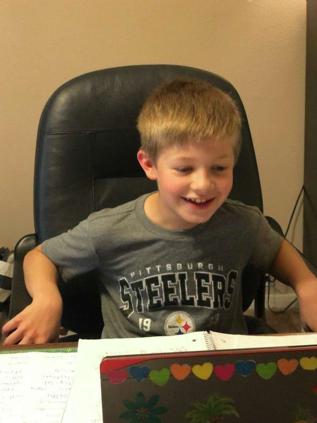 A Klein ISD student reacts to videoconferencing with his class for the first time March 26, 2020 during Week 1 of at-home learning for the school district.