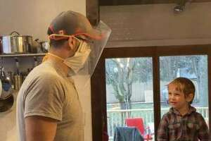 Dr. Daniel Barron and his son, Everett, make face masks with plastic shields for use by health care workers.