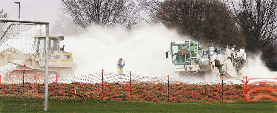 A spreader kicks up lime dust this week as it spreads the fine powder on the construction site for a new soccer field being installed in Alton's Gordon Moore Park. The lime dust is used to condition and dry fresh dirt to make it more managable.