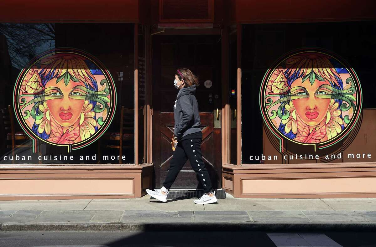 A woman wearing a face mask walks by the Soul de Cuba Cafe on Crown Street in New Haven on March 27, 2020.