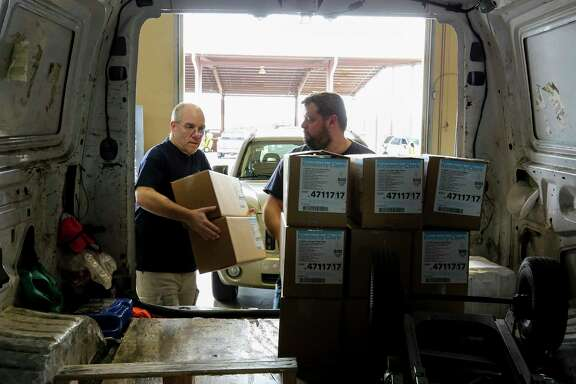SETRAC Emergency Operations' Donald Morrison, left, and Austen McMillin load up medical supplies into a van from Memorial Hermann Hospital at the Strategic National Stockpile distribution site Wednesday, March 18, 2020, in Houston.