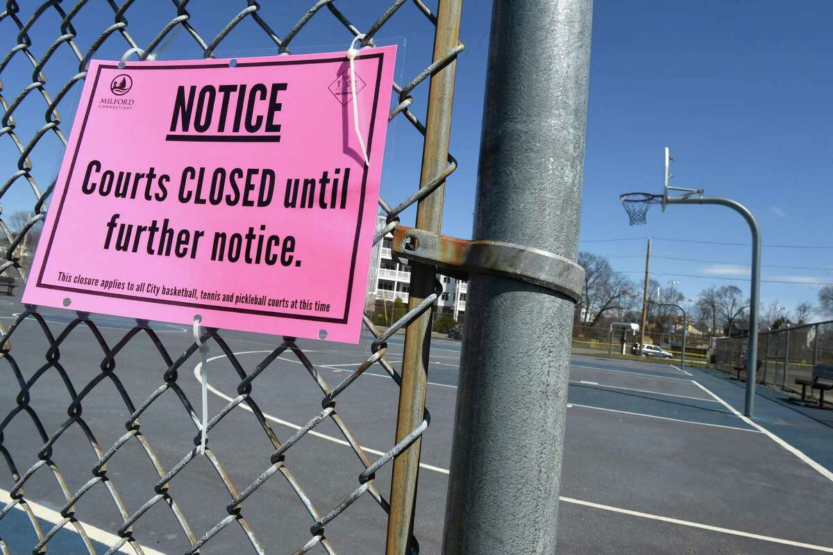 A notice that courts are closed until further notice hangs outside of the basketball courts behind the Milford Public Library on March 27, 2020.