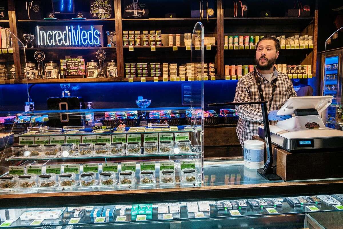 Sean Hair waits behind the counter for a customer at the Green Cross dispensary in San Francisco.