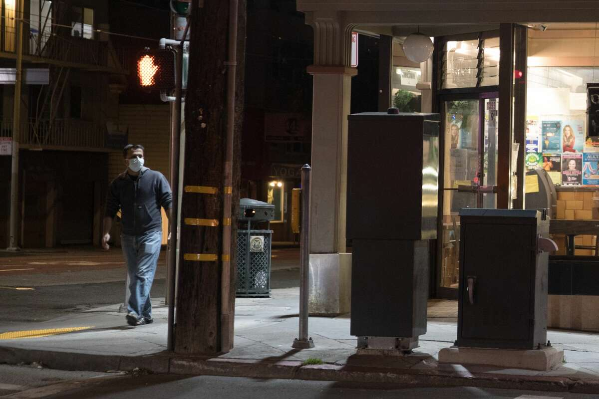 A man wearing a protective mask walks down Irving Street in the Sunset District. The normally bustling streets of San Francisco on March 26, 2020, are quiet after the city instituted a shelter-in-place order to prevent the spread of the COVID-19 coronavirus.
