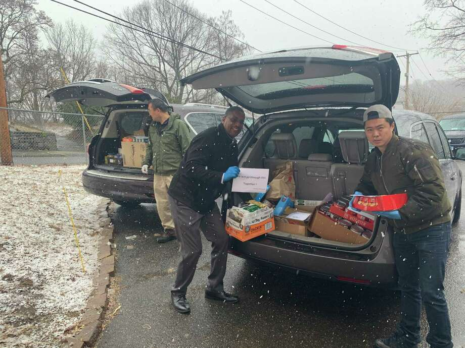 State Sen. George Logan, R-Ansonia, center, joins Jason Zhao and Han Chen, of Orange, left, in unloading two of the SUVs that delivered thousands of cans and pacakages of food to the Salvation Army Food Bank in Ansonia Monday. The food was a donation from the region's Chinese-American community. Photo: Michael P. Mayko / Hearst Connecticut Media