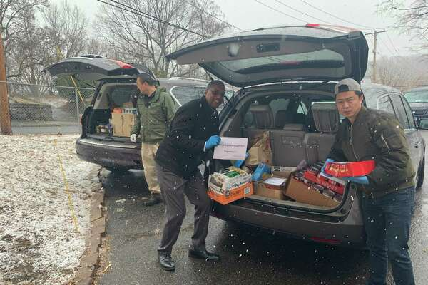 State Sen. George Logan, R-Ansonia, center, joins Jason Zhao and Han Chen, of Orange, left, in unloading two of the SUVs that delivered thousands of cans and pacakages of food to the Salvation Army Food Bank in Ansonia Monday. The food was a donation from the region's Chinese-American community.
