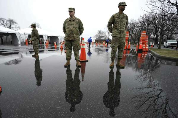 National Guard troops stand by as people wait to be tested at the State's First Drive Through COVID-19 Mobile Testing Center at Glen Island Park in New Rochelle, New York March 13, 2020. - Governor Andrew M. Cuomo on March 13, 2020 opened the states first drive-through COVID-19 mobile testing center in New Rochelle. (Photo by TIMOTHY A. CLARY / AFP) (Photo by TIMOTHY A. CLARY/AFP via Getty Images)