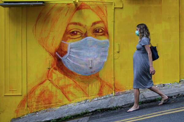 A pregnant woman wearing a face mask as a precautionary measure walks past a street mural in Hong Kong, on March 23, 2020.