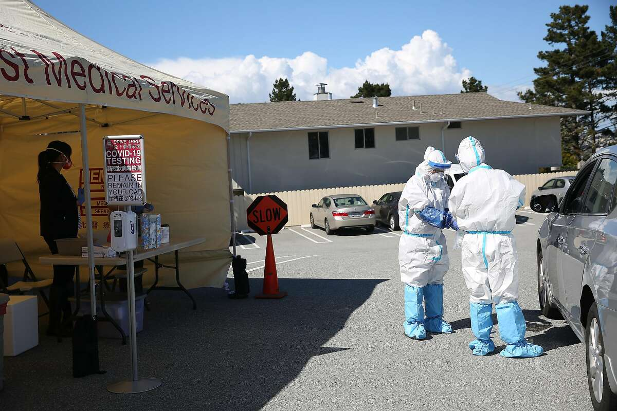Sandar Htun, M.D. (right) and Whitney Lao (second from right), medical assistant, work as they conduct COVID-19 tests at a drive-through testing site in the parking lot at the North East Medical Services Daly City Clinic on Thursday, March 26, 2020 in Daly City, Calif.