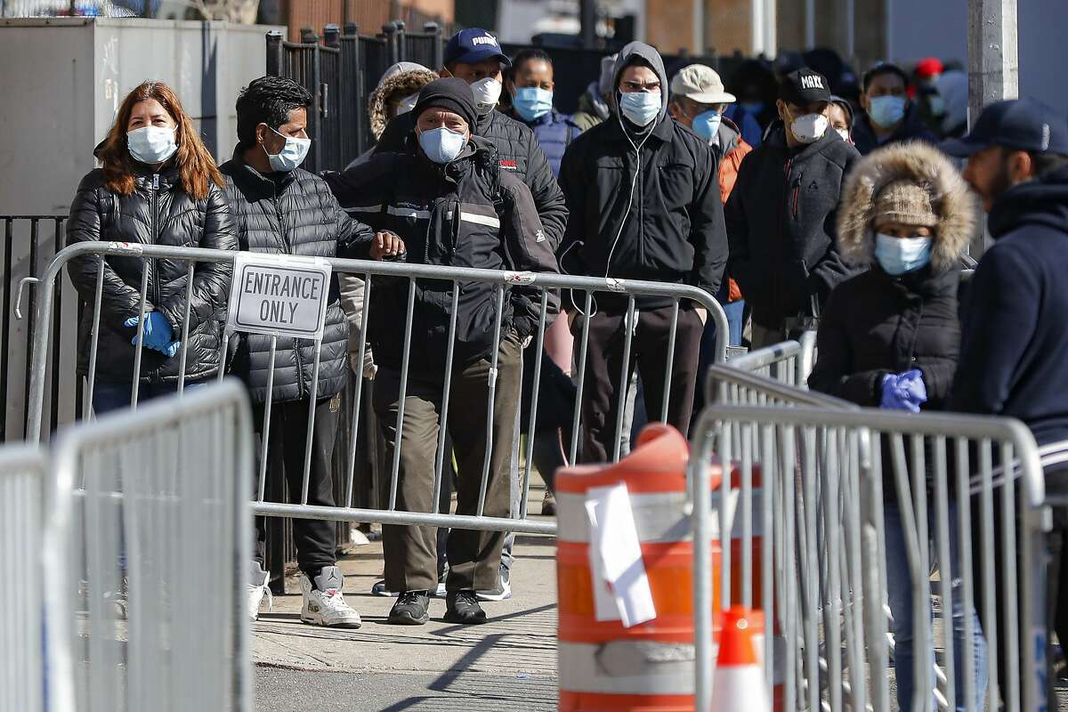 Patients wearing face masks and personal protective equipment wait on line for COVID-19 testing outside Elmhurst Hospital Center, Friday, March 27, 2020, in New York. The new coronavirus causes mild or moderate symptoms for most people, but for some, especially older adults and people with existing health problems, it can cause more severe illness or death. (AP Photo/John Minchillo)