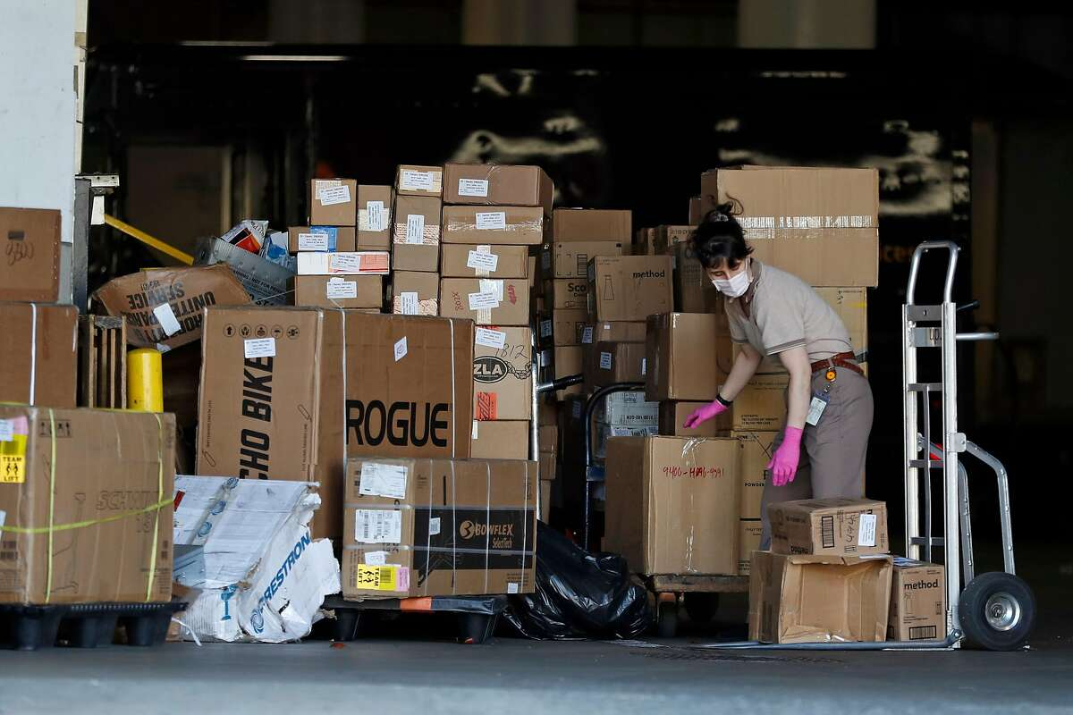 A worker moves packages at UPS facility on San Bruno Avenue in San Francisco, Calif., on Thursday, March 26, 2020.