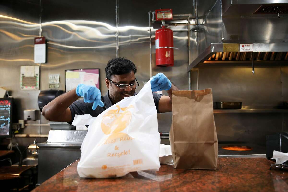 Employee Jay Sur prepares a food order for pickup at Pakwan, a Pakistani Indian restaurant, located at 3180 16th St., on Saturday, March 21, 2020, in San Francisco, Calif.