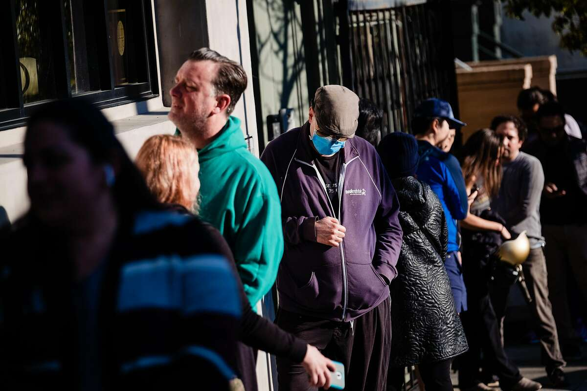 Customers are seen lining up at Che Fico Alimentari before takeaway service begins in San Francisco, Calif. on Saturday, March 21, 2020.