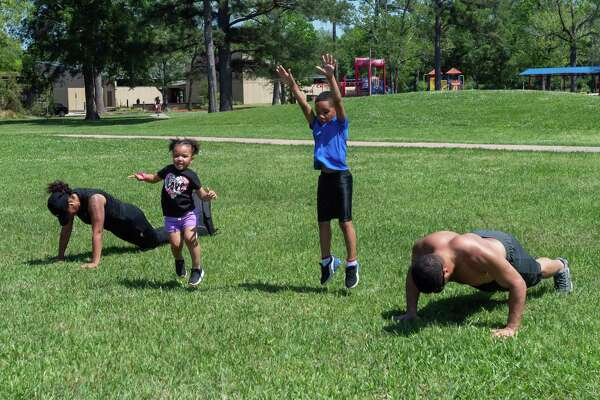 Emerie LeBlanc, 2, and her brother Braylon, 6, jump up after completing their push-ups while they exercise with their parents Brittney and EJ LeBlanc at Rogers Park on March 26, 2020. Fran Ruchalski/The Enterprise