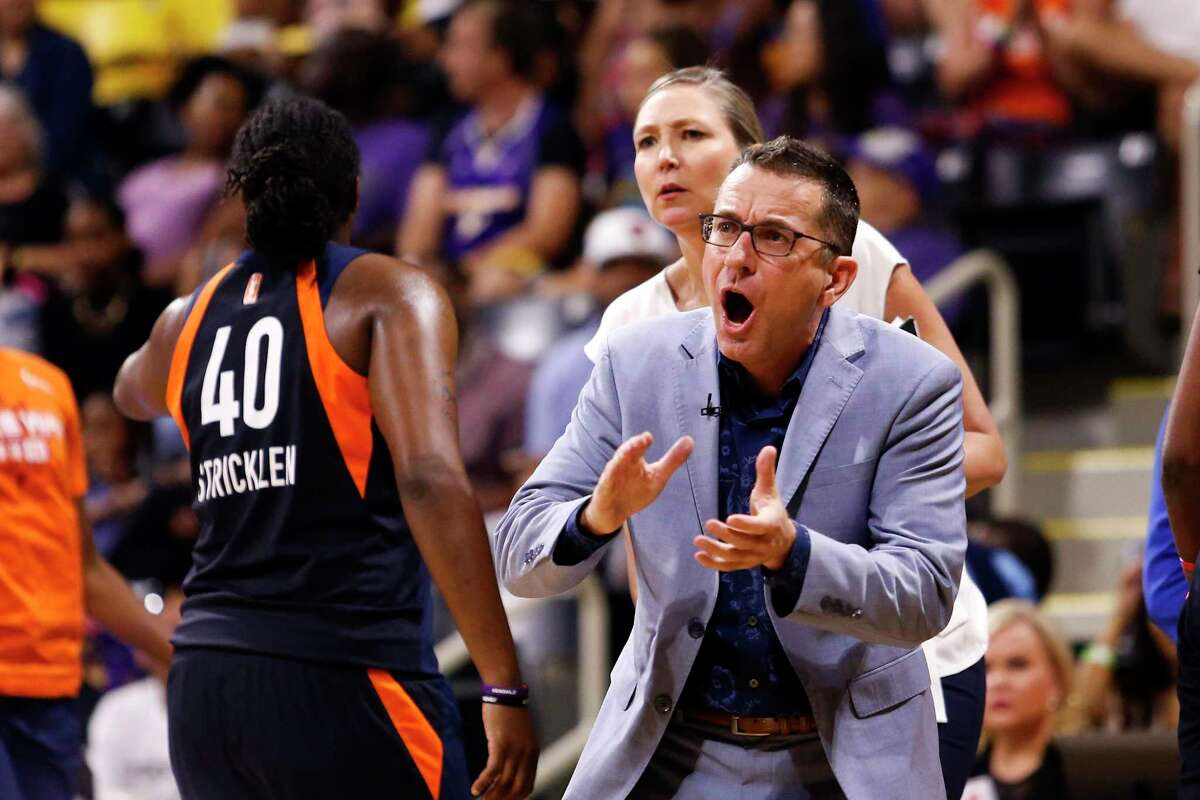 Connecticut Sun head coach Curt Miller, right, greets his players during a timeout in the second half of Game 3 of a WNBA playoff game against the Los Angeles Sparks in September.