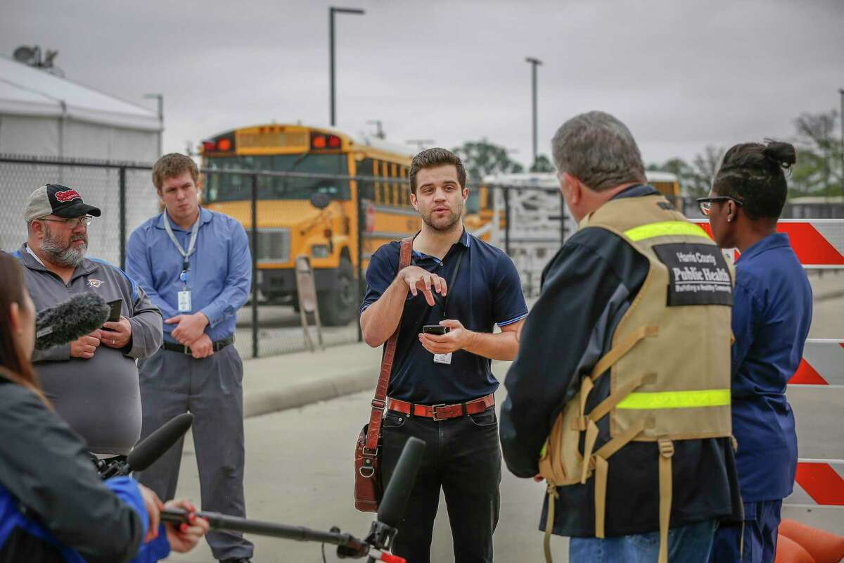 Houston Chronicle reporter Dylan McGuinness interviews Capt. Raquel A. Peat of U.S. Public Health Service and other officials at a COVID-19 testing site.