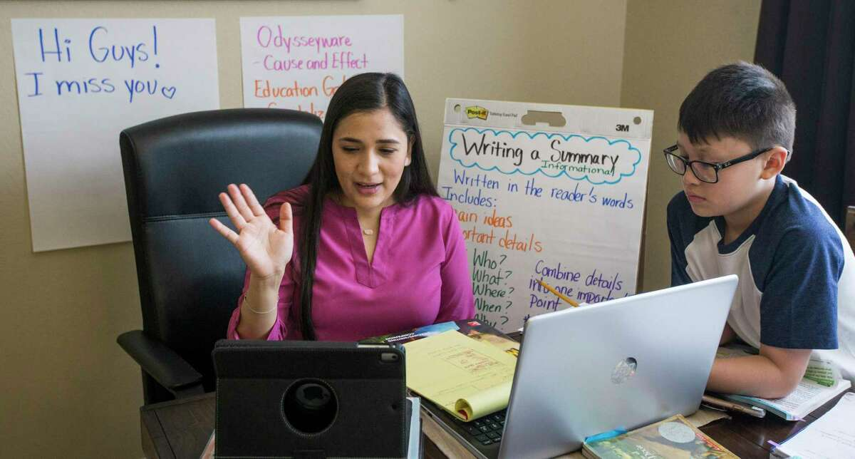 Elizabeth Ortega, a Royalwood Elementary School fourth-grade dual-language reading and writing teacher, waves goodbye to her students as she finishes a virtual lesson from her dining room with her son, Jacob, watching on Friday, March 27, 2020 in Houston. Ortega plans to meet with her two classes at least once a week through video conferencing.
