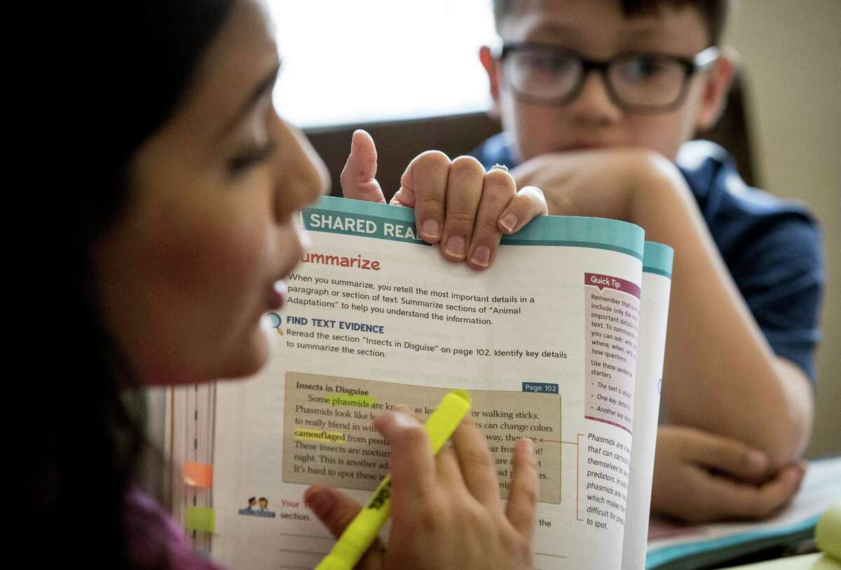 Jacob Ortega watches as his mother, Royalwood Elementary School fourth-grade teacher Elizabeth Ortega, delivers a language arts lesson from her dining room Friday, March 27, 2020 in Houston. About 30 out of Ortega's 40 students joined her two virtual classes.