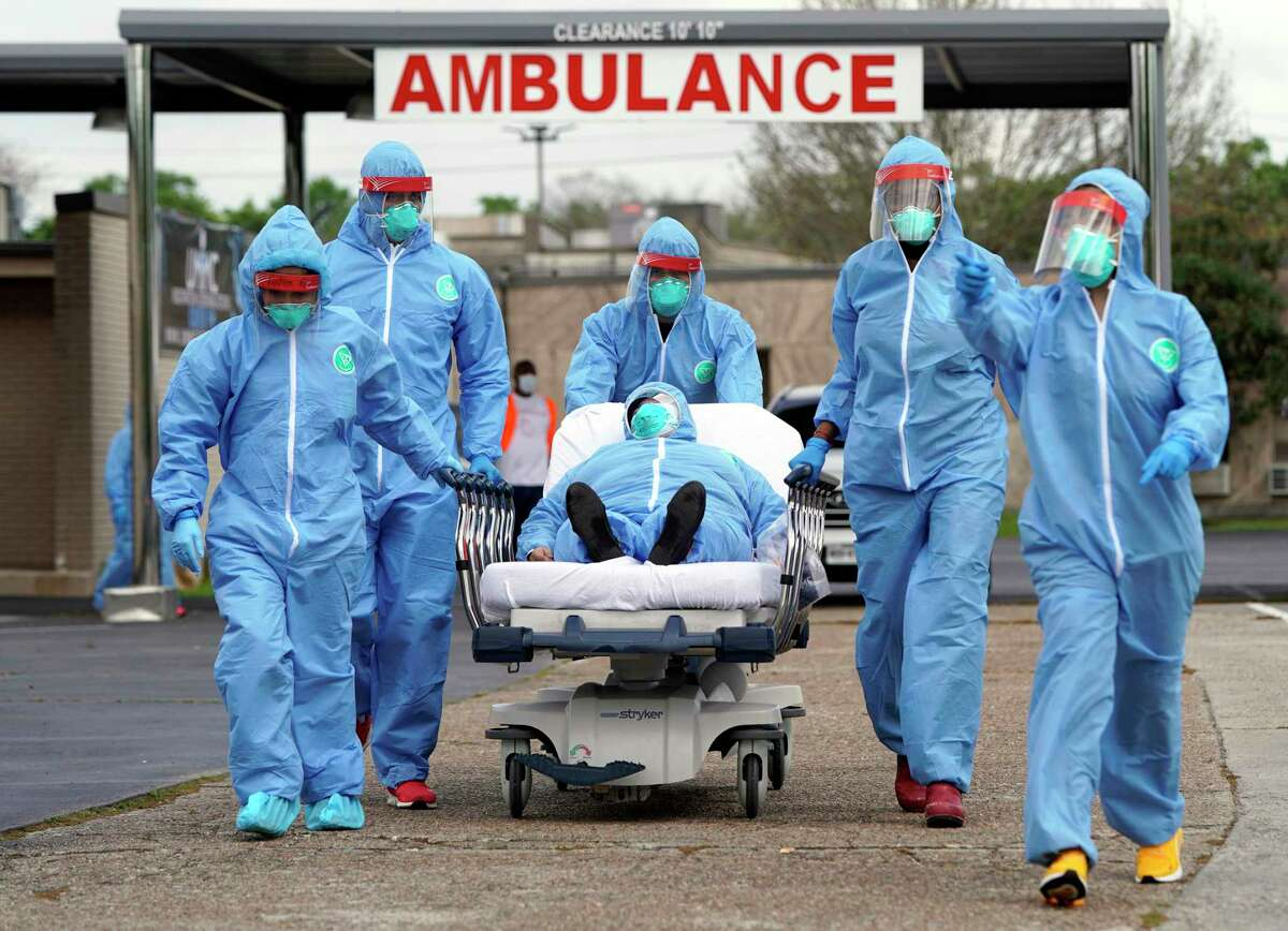 A person is taken on a stretcher into the United Memorial Medical Center after going through testing for COVID-19 on March 19, 2020, in Houston. People were lined up in their cars for more than two miles.