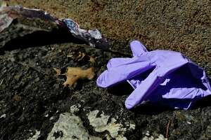 Shoppers dispose of their gloves on the ground after getting groceries from Super Stop and Shop in Norwalk, Conn.