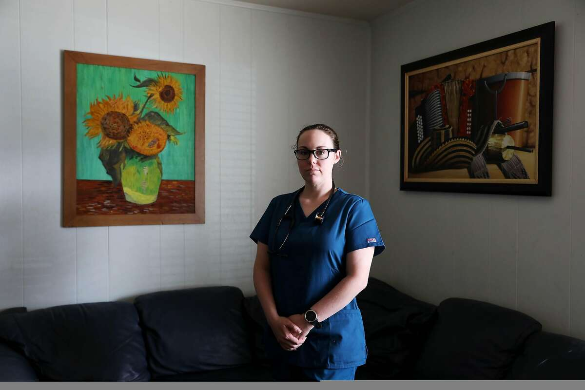 Jessica Boykin, 32, poses for a portrait in her home on Friday, March 27, 2020, in Napa, Calif. Boykin had stuck plenty of people with needles by the time she graduated from the nursing school at Los Medanos College in 2018, but nothing prepared her for the coronavirus pandemic. Now she's an ER nurse on the frontlines, where equipment and staff are short. Many nursing students who are just inches away from graduation are hoping to join her, and begging the state to bend its licensing rules so they can work.