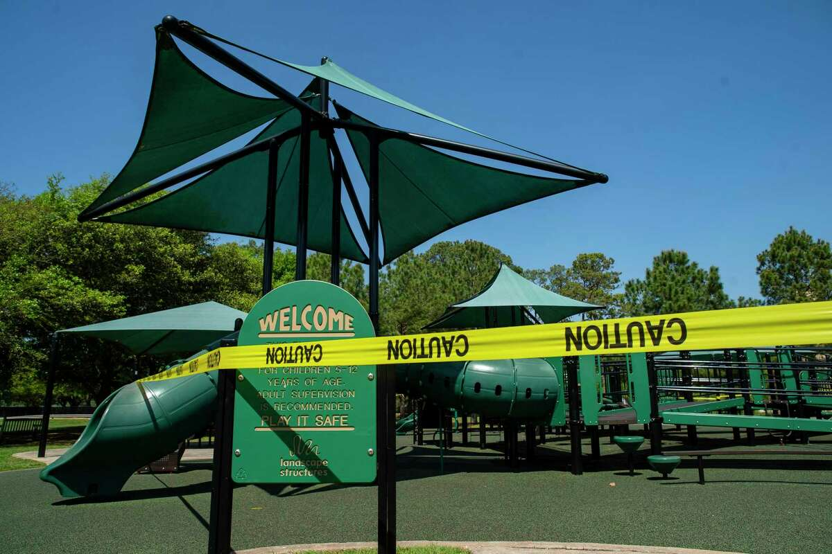 Playground equipment is surrounded by caution tape to signals its closure, Wednesday, March 25, 2020, at Memorial Park in Houston.