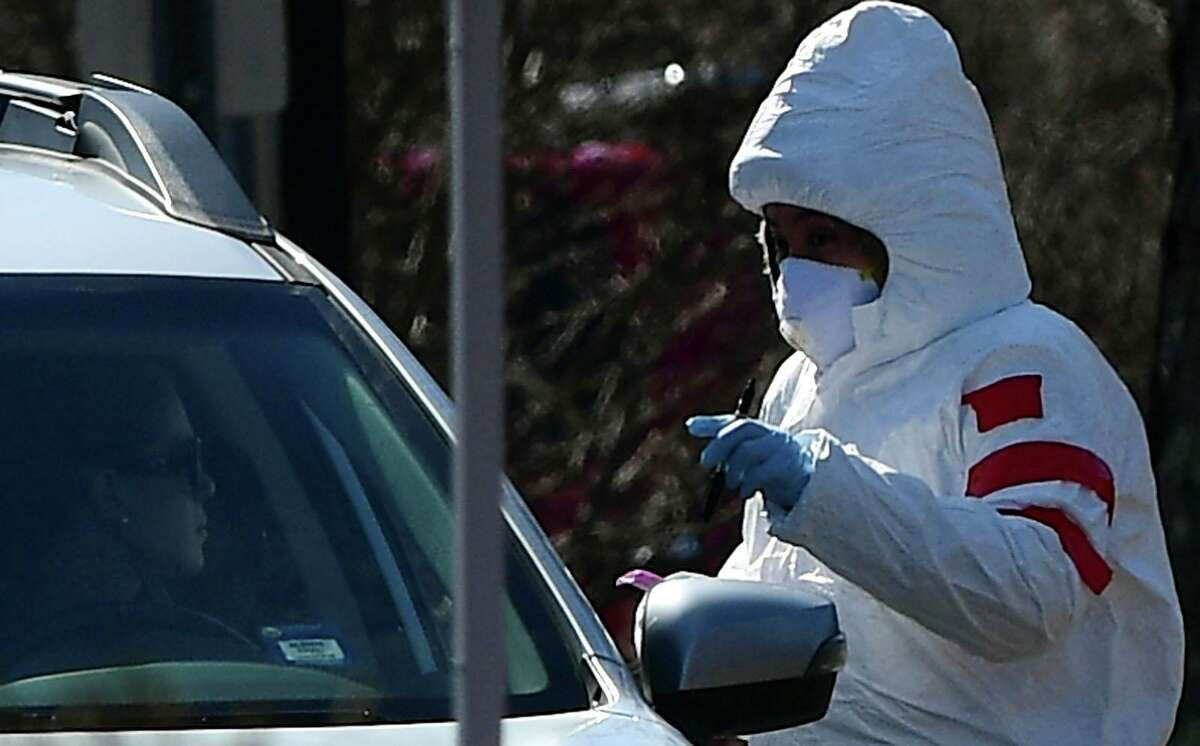Workers with Murphy Medical Associates conduct corona virus at a drive-thru testing station Tuesday, March 24, 2020, at Bedford Middle School in Westport, Conn.