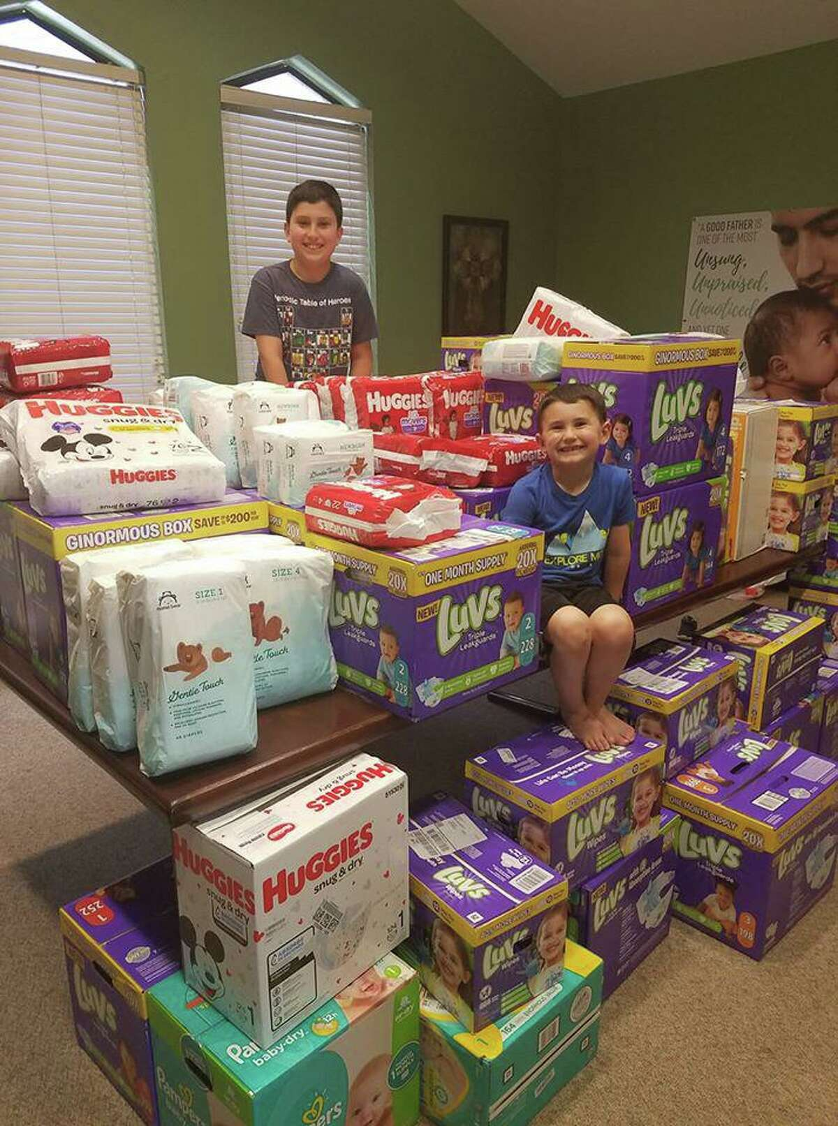 Jackson Goodman, 10, is all smiles in back while little brother Greg Goodman, 5, strikes a similar pose with the donations they have gathered for the Pregnancy Help Center of West Houston.