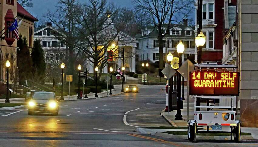 In this Thursday, March 26, 2020 photo, an electronic sign in downtown Westerly, R.I., informs motorists coming of a quarantine policy announced by Gov. Raimondo. Travelers from New York will be required to self-quarantine for 14 days upon arriving in the state. (Harold Hanka/The Sun via AP)
