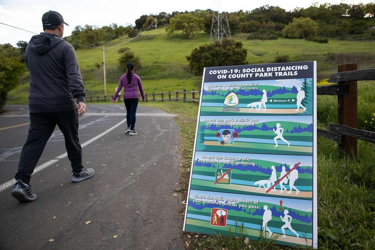 Walkers practice social distancing as the enter Santa Teresa County Park Thursday, March 26, 2020, in San Jose, Calif.