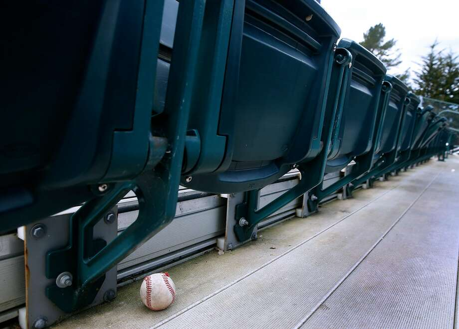 A tattered baseball rests below a row of seats behind home plate at Half Moon Bay High School in Half Moon Bay. Photo: Paul Chinn / The Chronicle