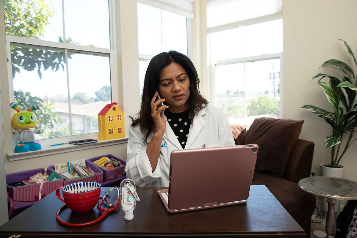 Dr. Prarthana Parmani, a pediatrician with Heal, conducts telemedicine from a makeshift office at home Thursday, March 26, 2020, in Sunnyvale, Calif.