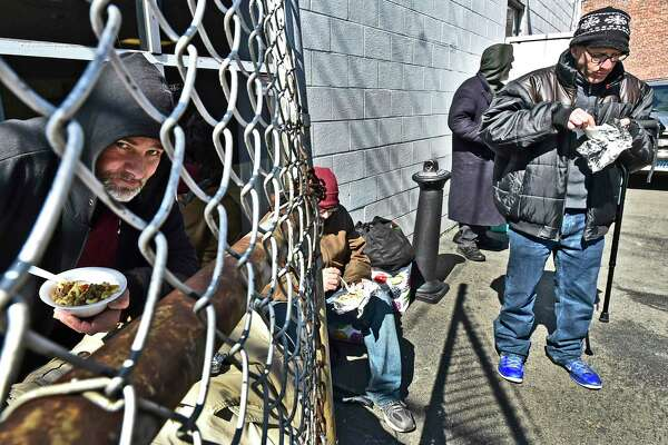 """New Haven, Connecticut - Friday, March 16, 2020: Raymond Brown, left, who spent the night at the emergency overflow homeless shelter, left, eats a """"lunch-to-go"""" Monday afternoon he received from the the 180 Center of New Haven homeless ministry on Grand Ave. in New Haven. Instead of entering the ministry building for breakfast and lunch due to guidelines set by the City of New Haven amidst the public health concern over the Coronavirus / COVID-19 outbreak, the ministry provided meals outside. """"I hope our country gets through this without many fatalities,"""" says Brown. At right, is Shayne Buckley of New London, who was released from prison and dropped off in New Haven, eats his lunch, far right."""
