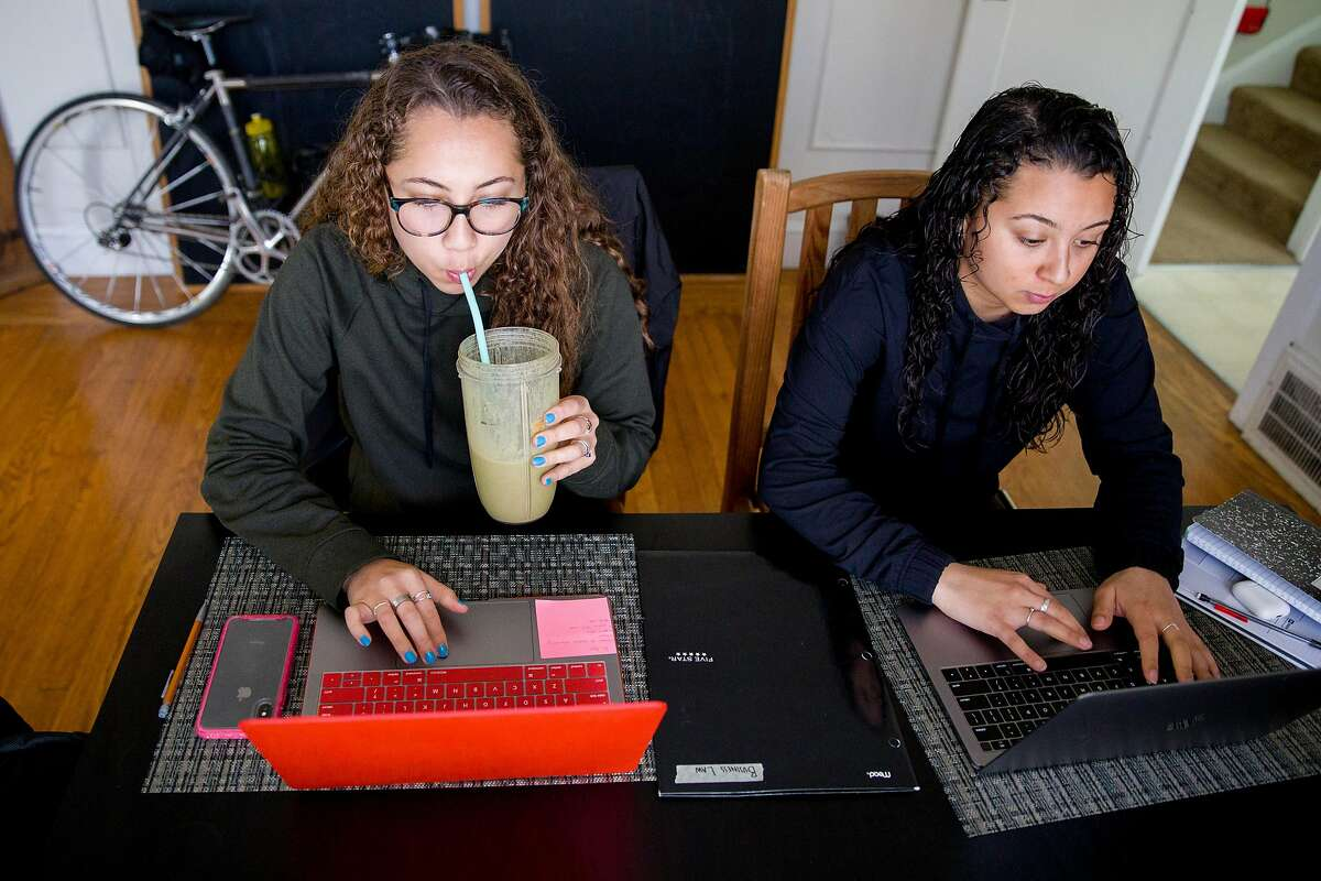 Anissa Perez, 18, (left) studies while sitting with her sister Marisol Perez, 15, at their home in Oakland, Calif. Thursday, March 26, 2020. Anissa, a freshman at University of Miami, is now living and studying from her parent's home where she shares a room with her 15-year-old sister. Schools across the country have closed due to the outbreak of the Coronavirus.