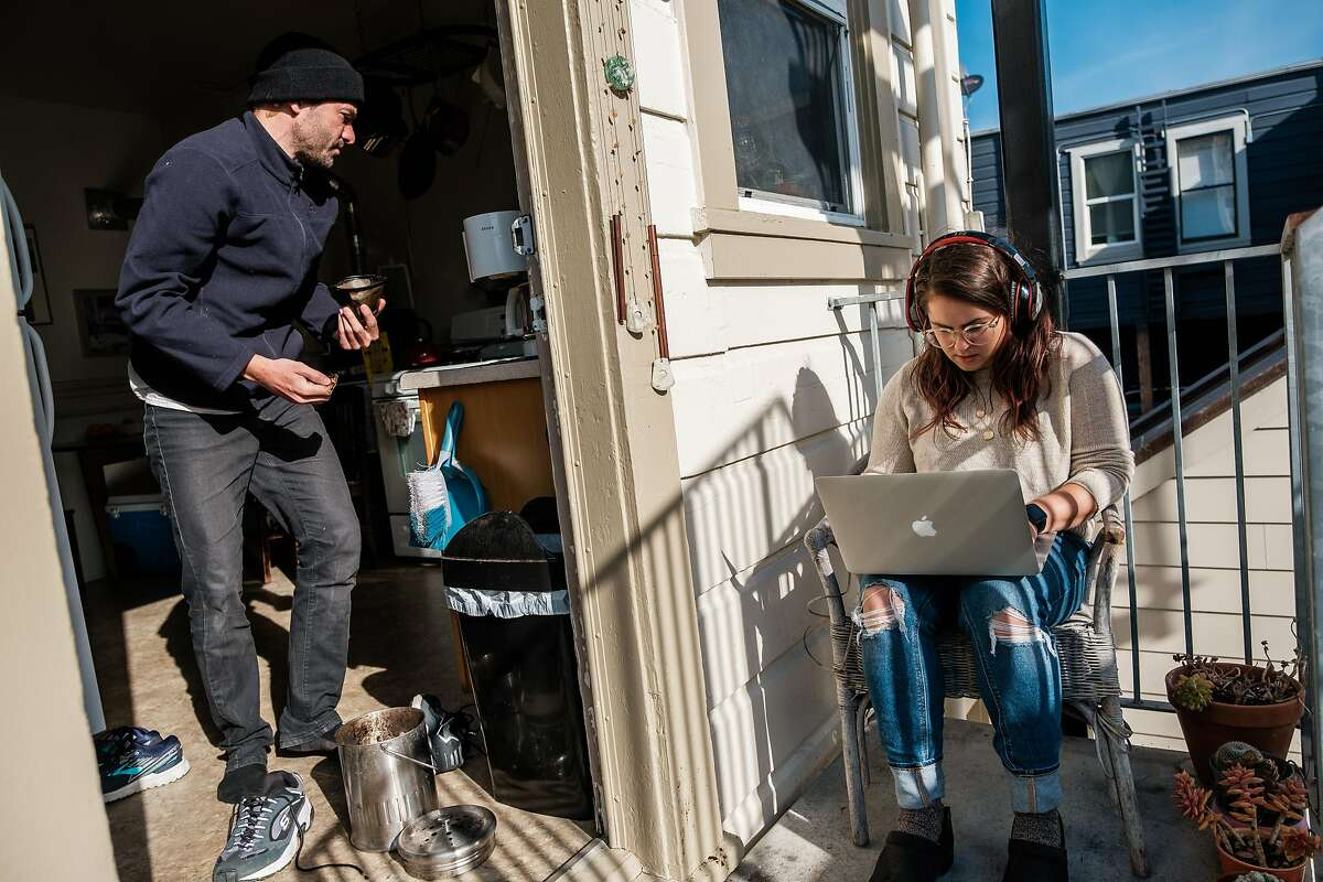 Tzipora Lederman, who works for the progressive political group Swing Left, works on her laptop on the balcony of her home while her partner Jon Moldover makes coffee in San Francisco, Calif. on Friday March 27, 2020.