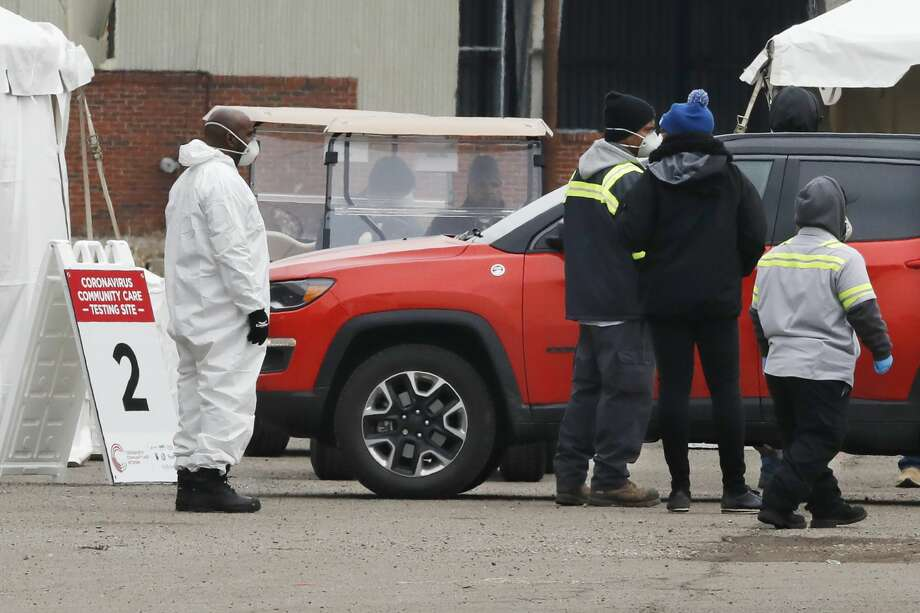 Health care officials watch as a vehicle approaches a testing site at the Michigan State Fairgrounds, Friday, March 27, 2020, in Detroit. The city set up several stations at the fairgrounds to allow for drive up testing for the coronavirus. (AP Photo/Carlos Osorio) Photo: Carlos Osorio/AP / Copyright 2020 The Associated Press. All rights reserved.