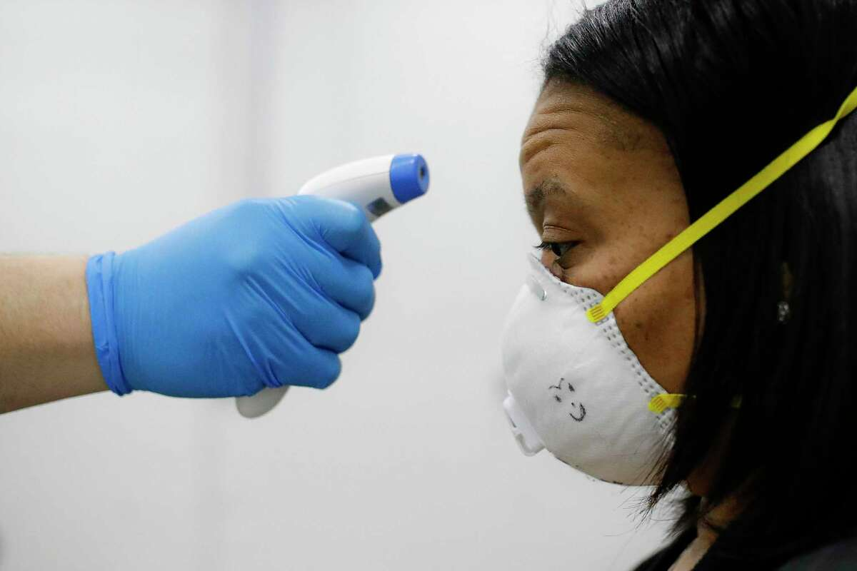 A worker wearing personal protective equipment has her temperature taken before entering a mass manufacturing operation to supply New York City government with splash guards for protection to distribute against COVID-19 transmission, Friday, March 27, 2020, at the Brooklyn Navy Yard in New York. The new coronavirus causes mild or moderate symptoms for most people, but for some, especially older adults and people with existing health problems, it can cause more severe illness or death. (AP Photo/John Minchillo)