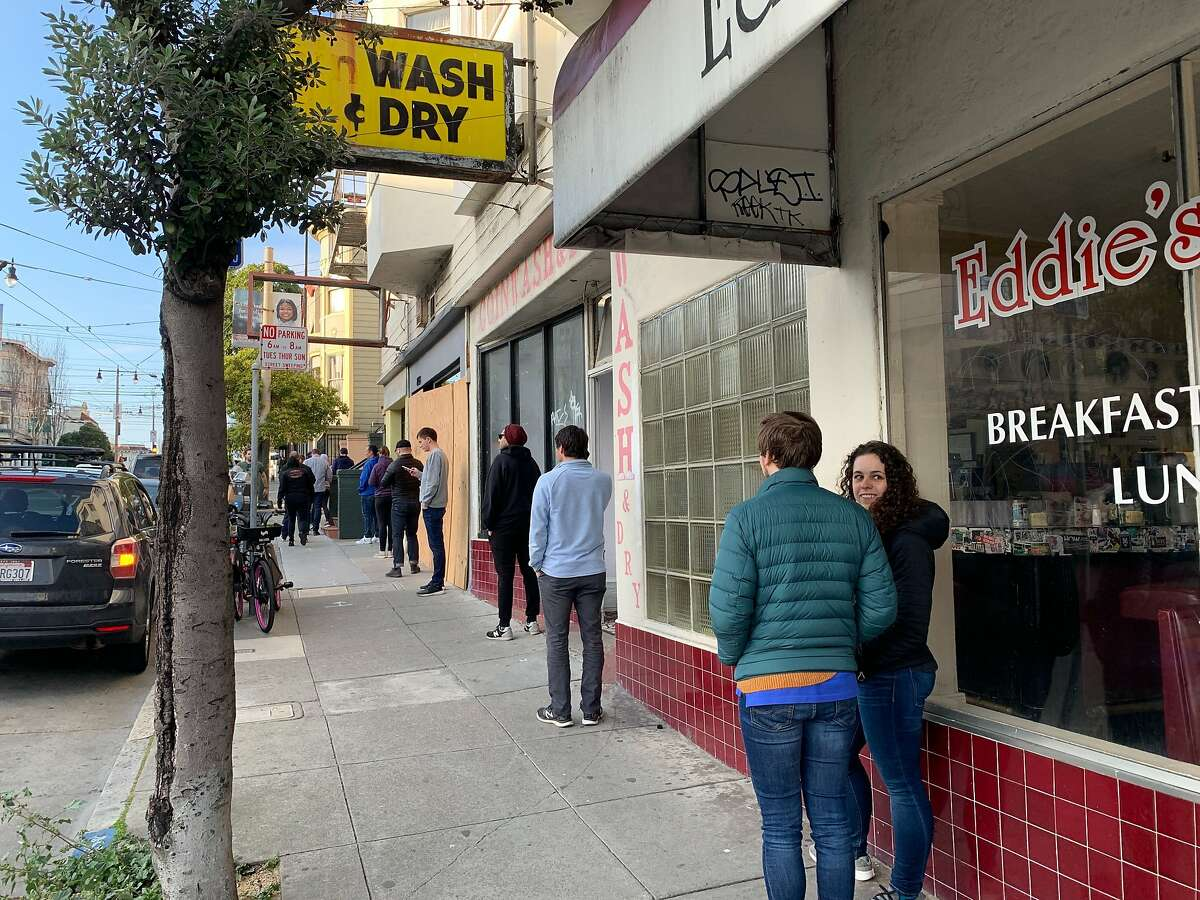 Observing a San Francisco health mandate to keep their distance from each other when going out, customers line up on Divisadero Street to pick up food from Che Fico on Friday, March 27, 2020, in San Francisco, Calif.