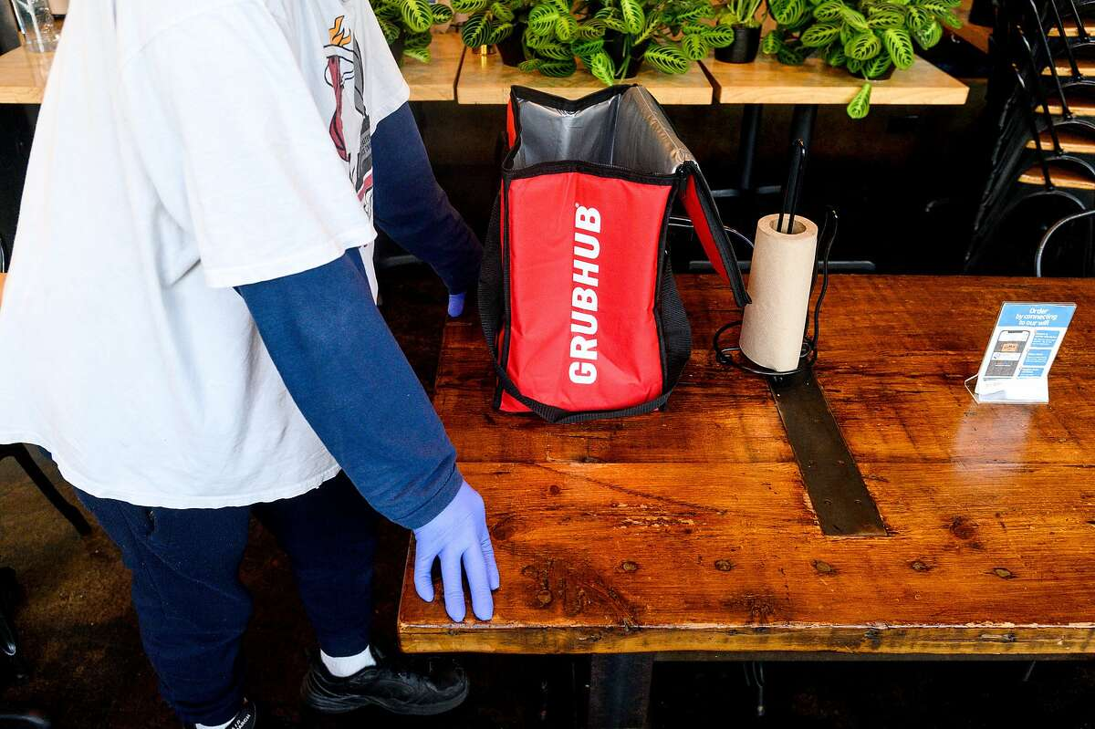 A Grubhub driver waits for an order at a Bay Area restaurant. The delivery company is facing a lawsuit alleging trademark infringement.