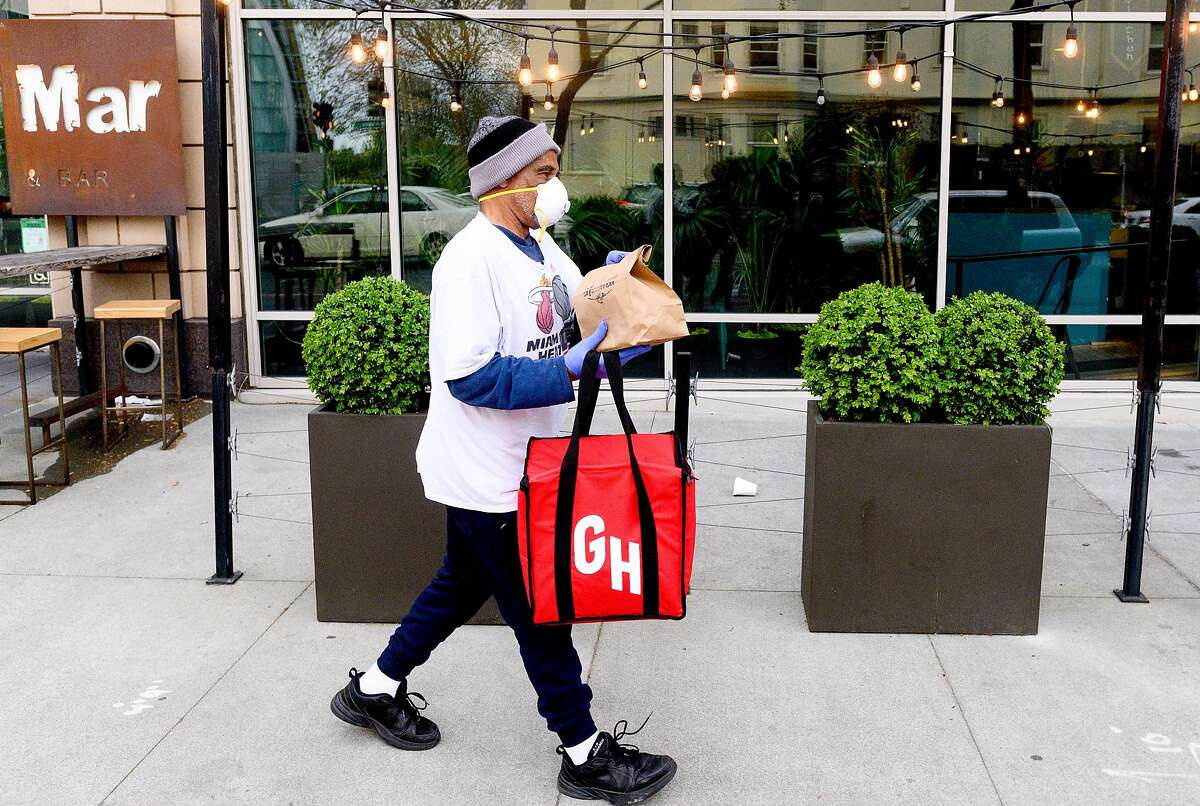 Grubhub driver David Augusta carries an order from alaMar on Friday, March 27, 2020, in Oakland, Calif. The restaurant has seen business increase as customers seek take-out and delivery options under coronavirus stay-at-home orders.