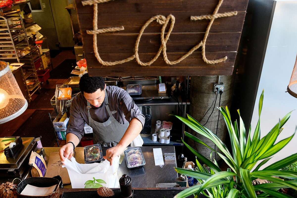 Chef Nelson German prepares a delivery order at alaMar on Friday, March 27, 2020, in Oakland, Calif. The restaurant has seen business increase as customers seek take-out and delivery options under coronavirus stay-at-home orders.