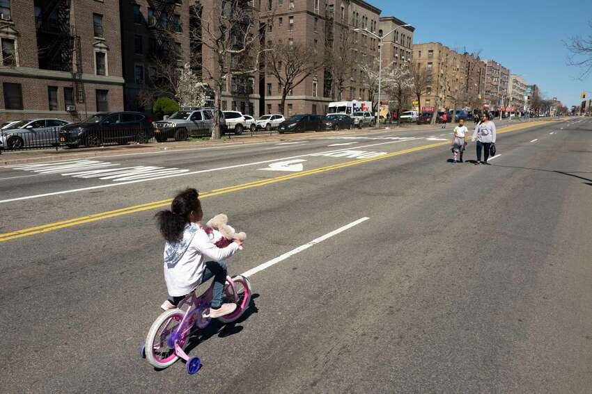 Victoria Scott bicycles along a section of the Grand Concourse that has been temporarily closed to vehicular traffic as the city tests out a pilot program providing more social distancing space during the coronavirus pandemic, Friday, March 27, 2020 in the Bronx borough of New York.