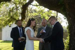 Pastor Jeffrey Johnson offers an opening prayer before Isabelle and Ben Moore are wed beneath the large oak tree at Isabelle's home in Beaumont Friday before a small group of family attend. The couple originally had a group of over 200 planning to attend, including family from out of town. Due to the coronavirus and crowd limitations, they opted to go ahead with the ceremony, albeit with a far smaller group of close family attending. Photo taken Friday, March 27, 2020 Kim Brent/The Enterprise