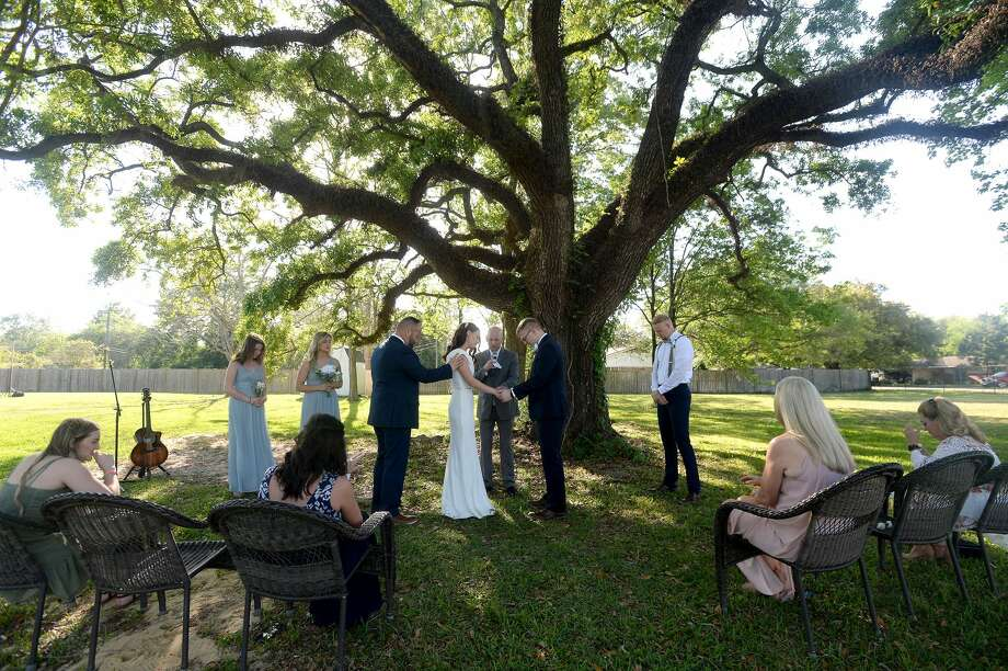 Isabelle and Ben Moore are wed beneath the large oak tree at Isabelle's home in Beaumont Friday, as a small group of family attend. The couple originally had a group of over 200 planning to attend, including family from out of town. Due to the coronavirus and crowd limitations, they opted to go ahead with the ceremony, albeit with a far smaller group of close family attending. Photo taken Friday, March 27, 2020 Kim Brent/The Enterprise Photo: Kim Brent/The Enterprise