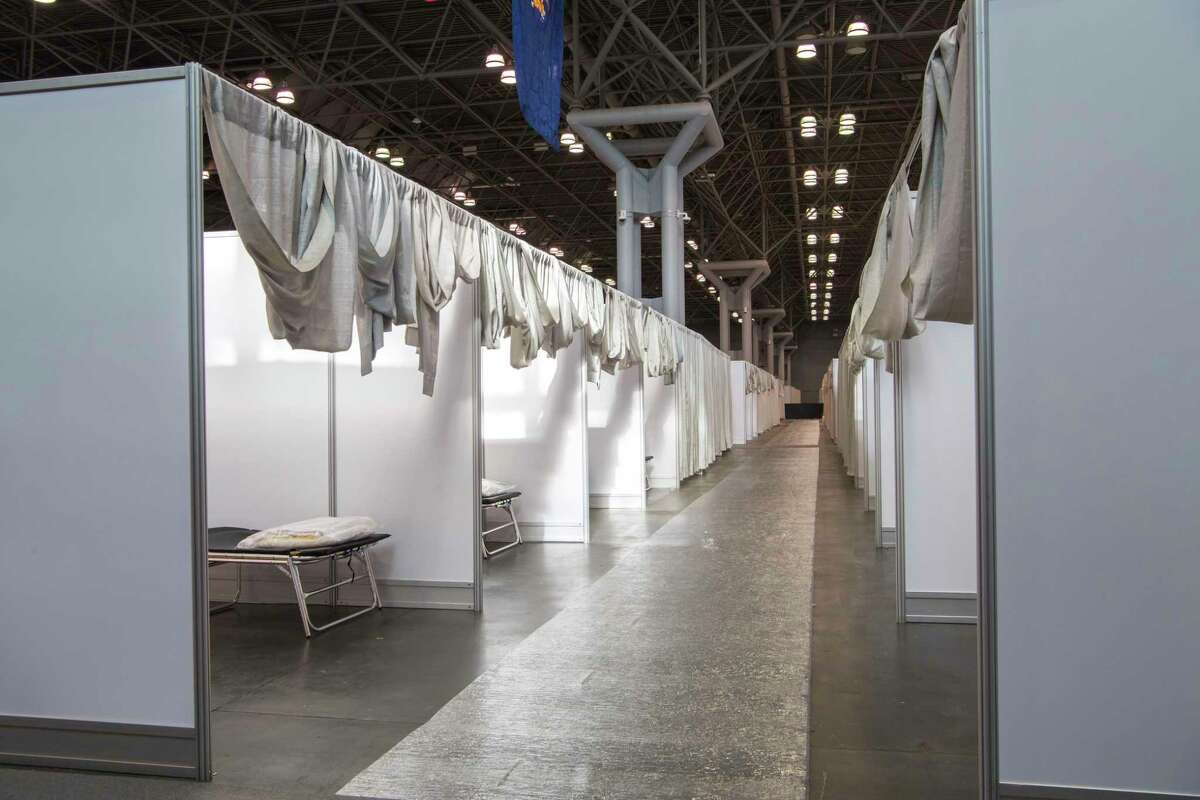 In this Friday, March 27, 2020 photo provided by Office of Governor Andrew M. Cuomo, makeshift hospital rooms stretch out along the floor at the Jacob Javits Convention Center in New York. New York Gov. Cuomo said the state wants to build four more temporary hospitals in New York City within weeks, before coronavirus cases are projected to peak. (Darren McGee/Office of Governor Andrew M. Cuomo via AP)