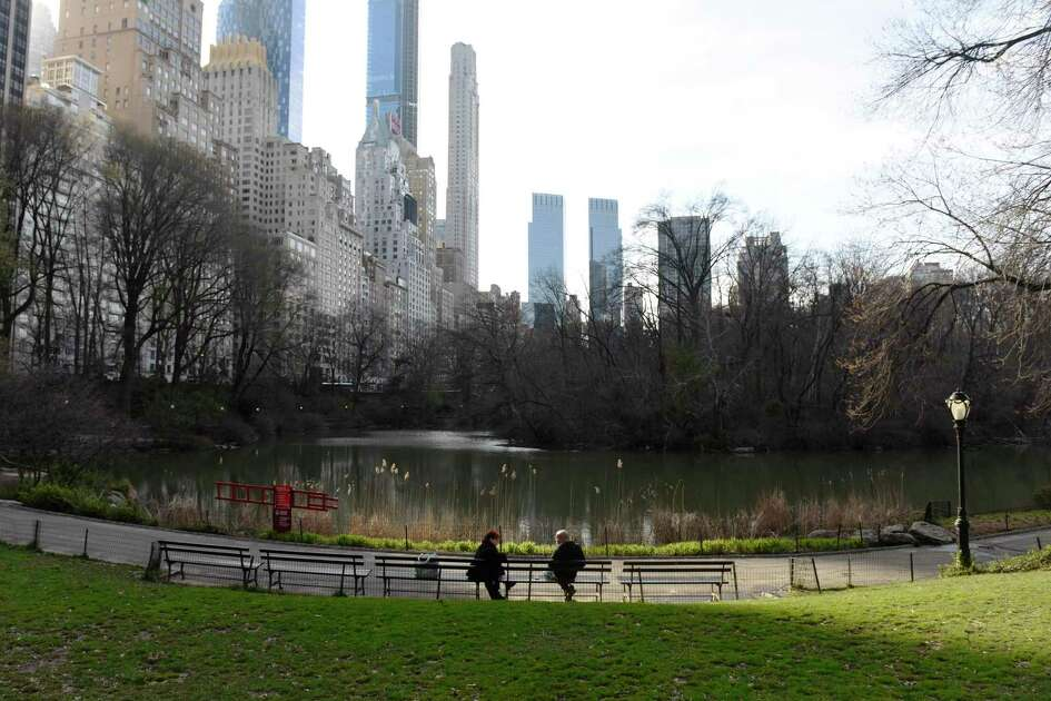 Two people sit at chat on a bench in a quiet Central Park in New York City on Thursday, March 26, 2020. New York City continues to see more new cases of the coronavirus than anywhere else in the country, and city streets have become relatively quiet with most businesses closed and Subway service limited.