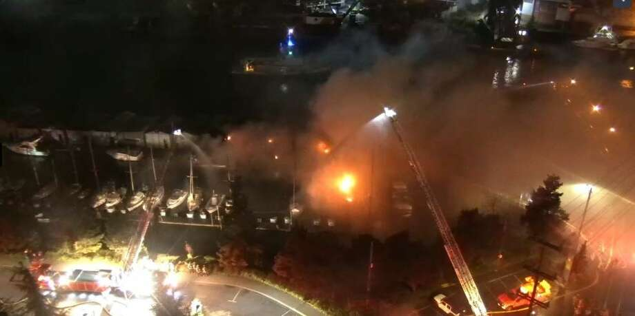 Firefighters battle a marina fire under the West Seattle bridge. Photo: SDOT Camera