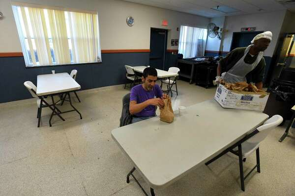 Jose Lopez, a guest of Pacific House, unpack a bag lunch he received at the homeless shelter on March 27, 2020 in Stamford, Connecticut. Pacific House staff are providing a safe enviorment for its guests by serving breakfast, lunch and dinner in shifts, limiting seating to small groups of two at a table and spacing the tables further apart, in response to promoting social distancing and eliminating contact with individuals.