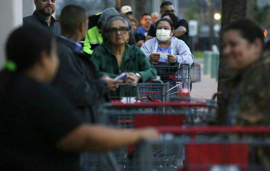 Shoppers, including Juana R. Mendez, right, line up early to be the first ones to get in at the Deco District H-E-B, on Monday, March 16, 2020. Mendez said she suffers from asthma and allergies, and always has masks, gloves and hand sanitizer to use when shopping. Photo: Bob Owen / Bob Owen/Staff Photographer / ©2020 San Antonio Express-News